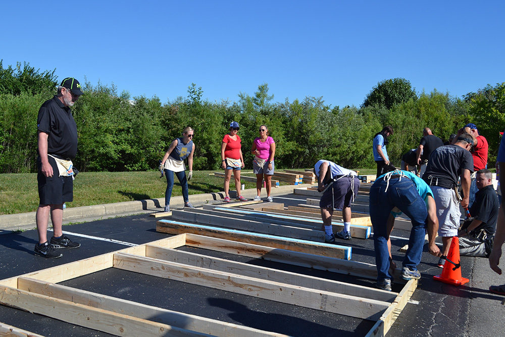 OW employees work on wood paneling during Habitat for Humanity Build