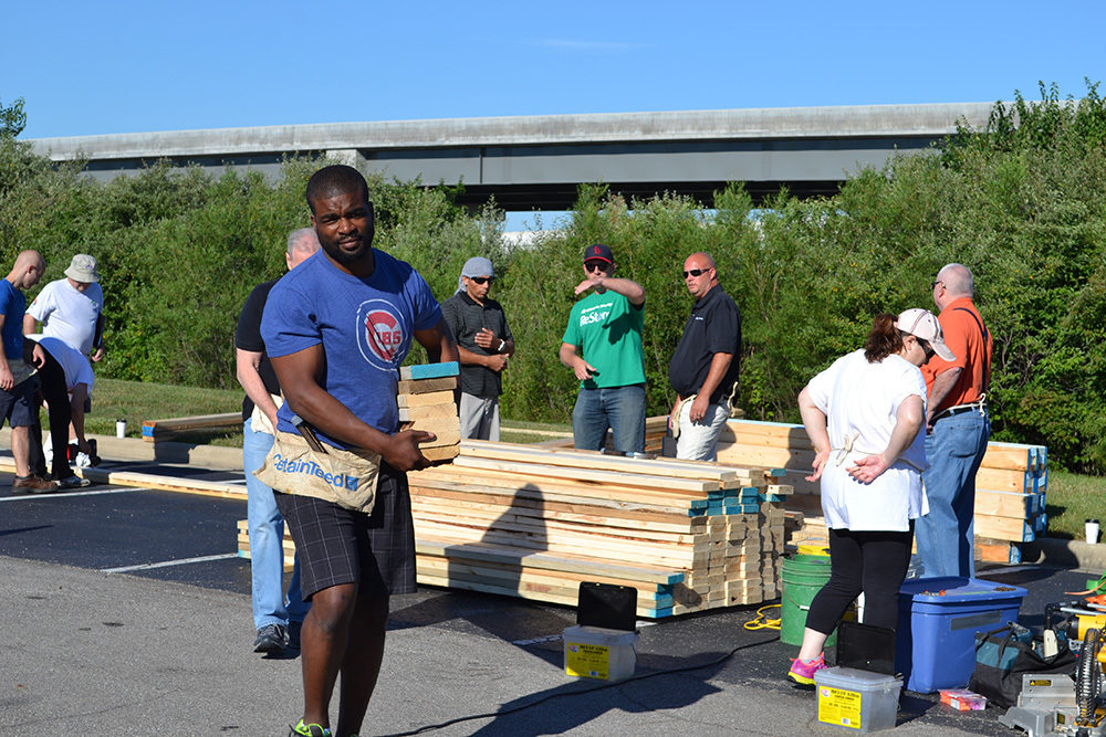 OW employees carrying lumber during Habitat for Humanity Build