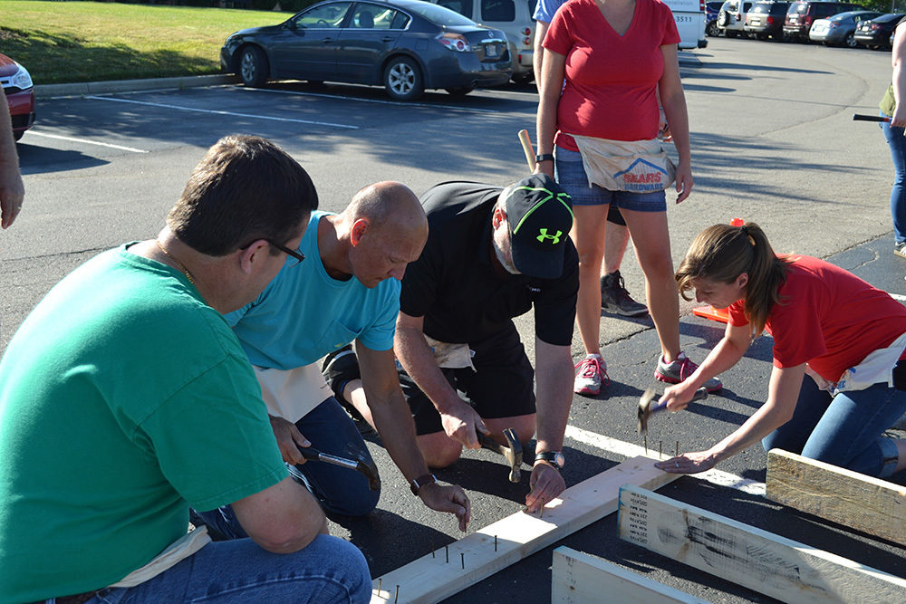 OW employees hammer wood during Habitat for Humanity Build