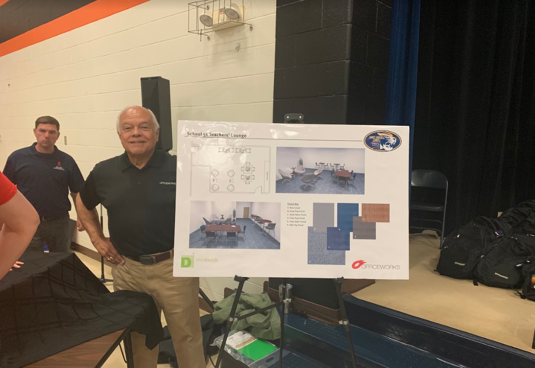 Tom posing with design plans of teachers lounge renovation at IPS School 51