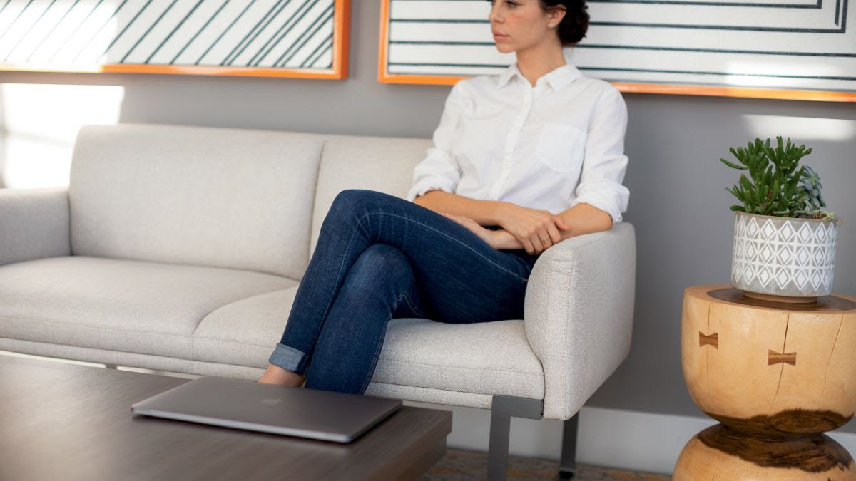 Staged image of woman sitting on Cameo lounge seating/sofa