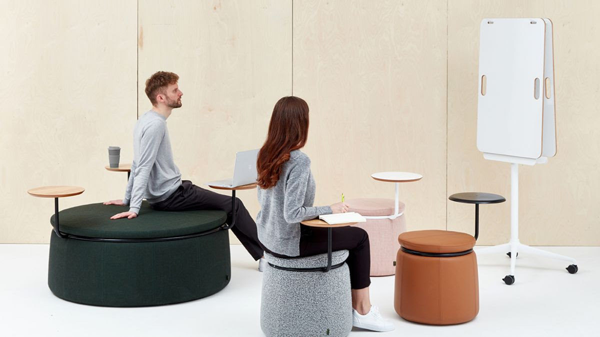 Staged photo of 2 people sitting on Naughtone Lasso Stools