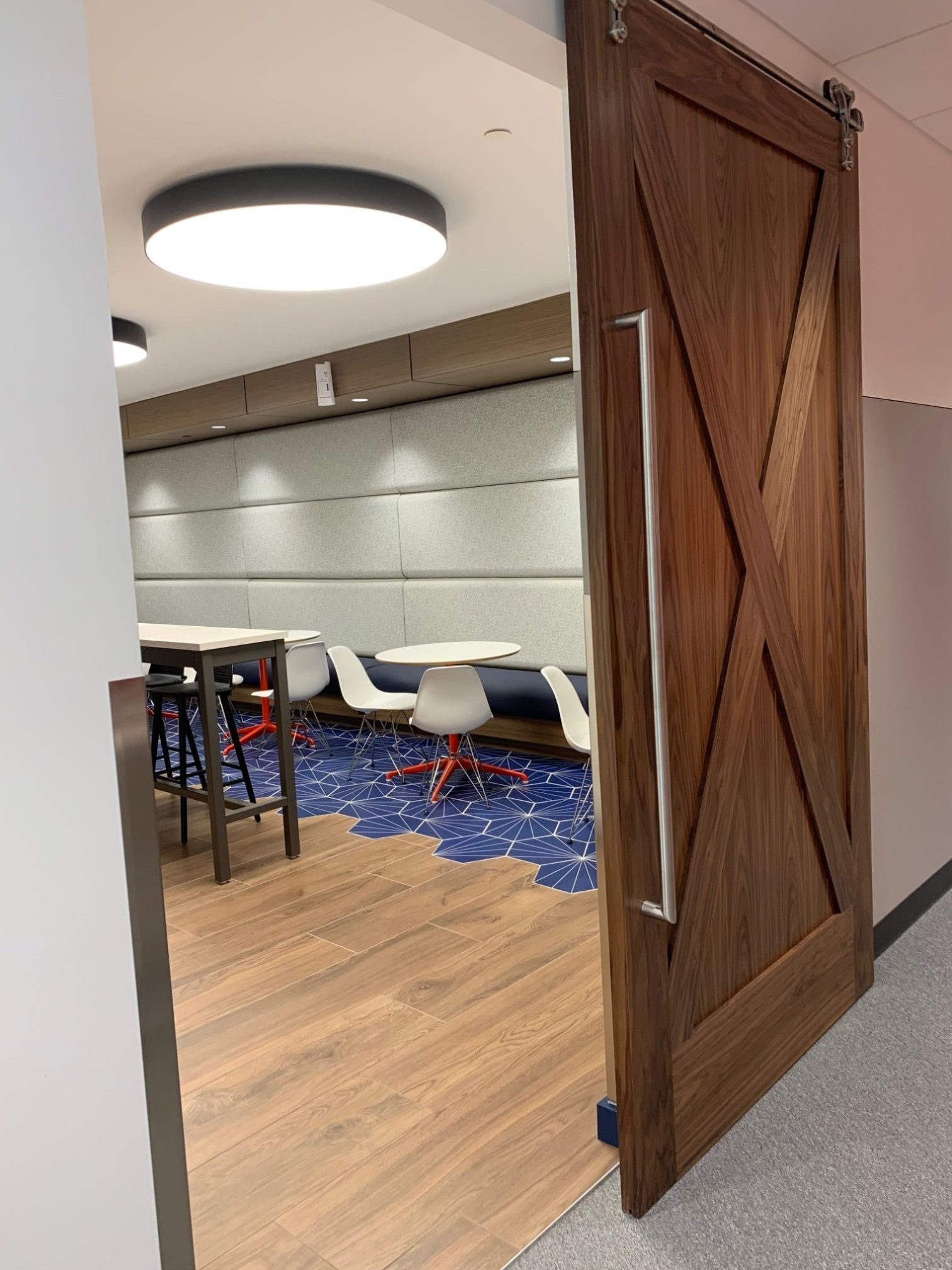 A sliding barn door opening into a dining area at the Goodman Campbell Brain and Spine center