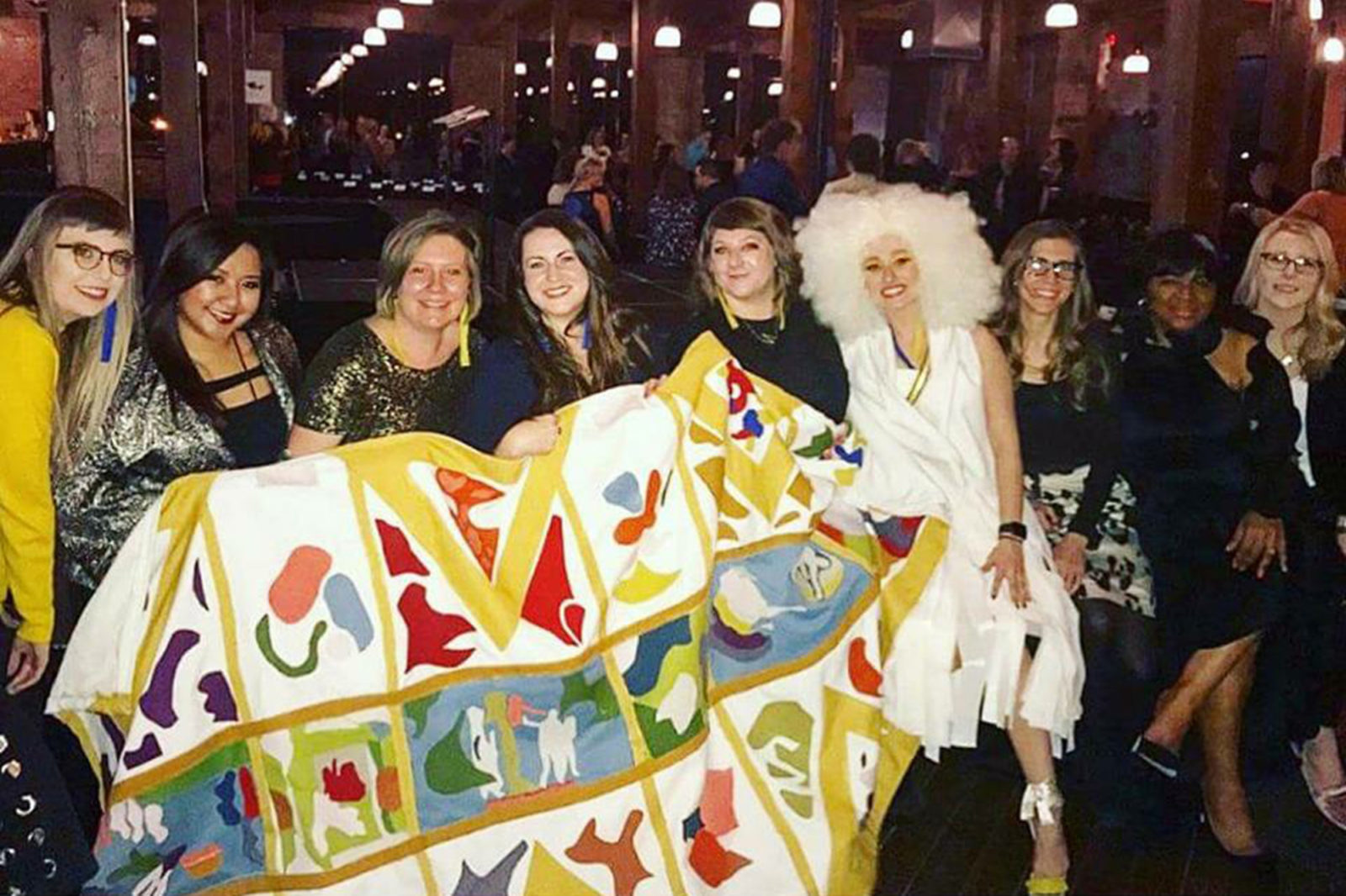 OfficeWorks design team and model pose with the colorful statement piece of the garment at IIDA Fashion Show