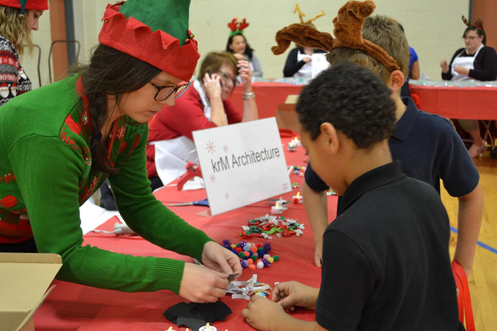WeCare event 2018: elf volunteer helps children with craft