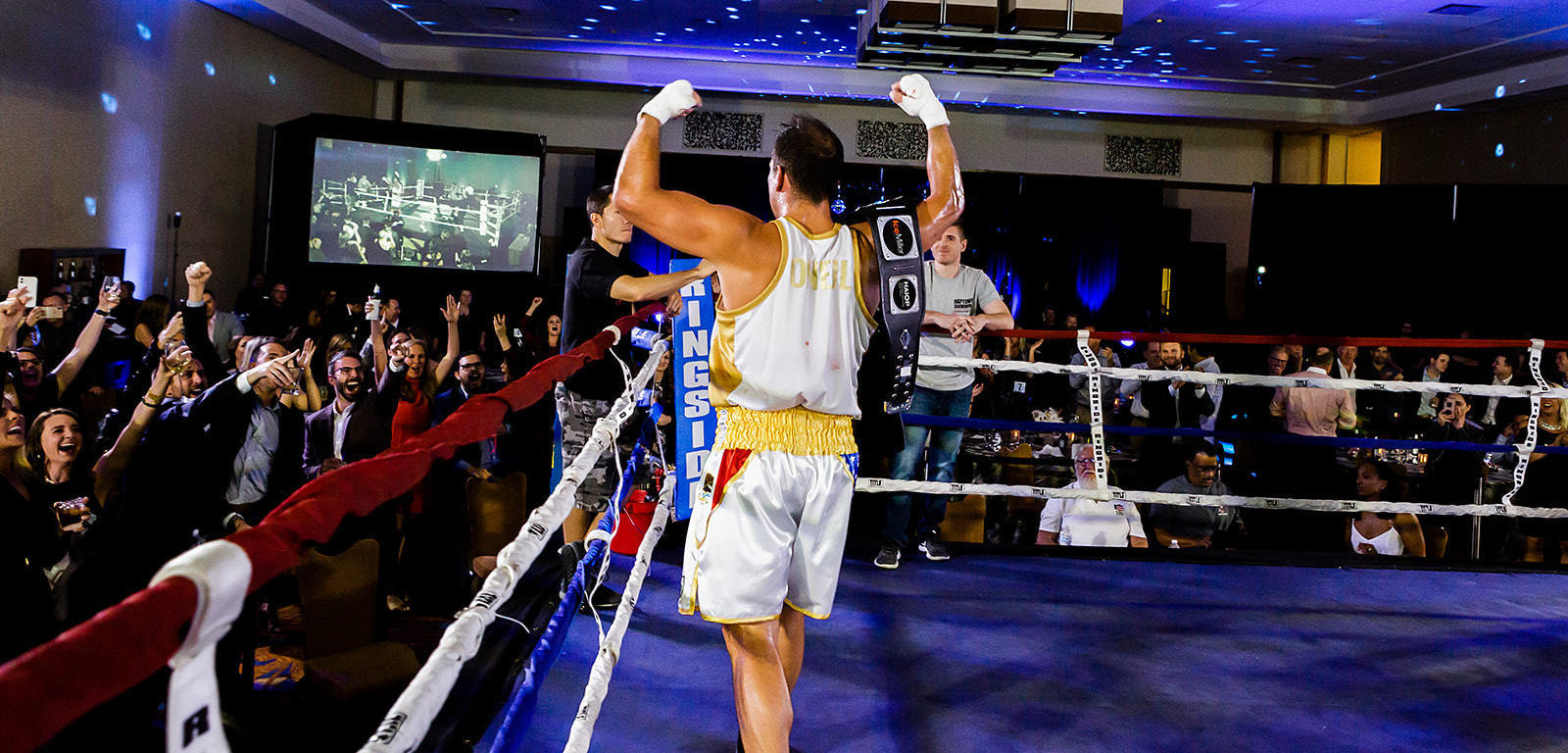 Rear photo of Scott O'Neil flexing to the crowd after winning charity boxing competition