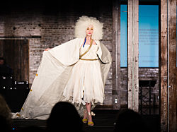 Model walking the runway at IIDA fashion show wearing dress designed by OfficeWorks staff