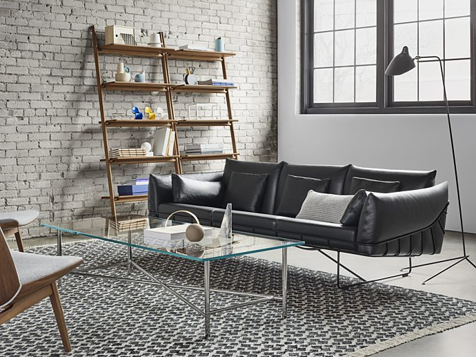 Design within reach couch with coffee table and storage product in background