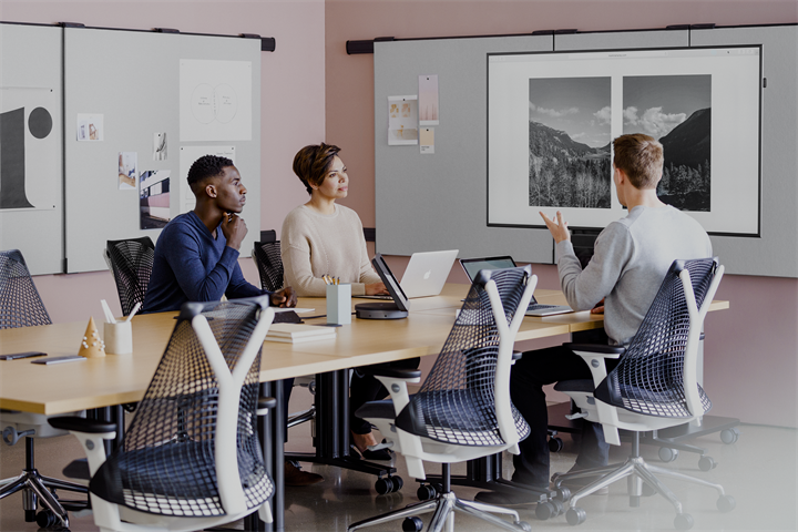 Stock image of 3 people meeting surrounded by Herman Miller office furniture