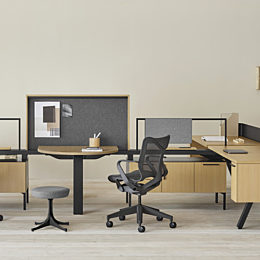 A Canvas Vista workstation in light wood and black with modesty screen, grey fabric panel, and black Cosm office chair.