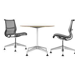 Round Setu Table centered between two Setu chairs