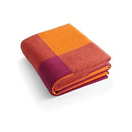 A folded Girard Throw blanket in shades of orange and magenta