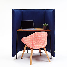 A red patterned Always Side Chair at a deep blue naughtone Cloud 1.5 Desk holding an open laptop and small cactus.