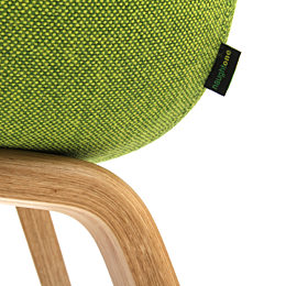 Close-up detail of the naughtone tag on the back left corner of an Always Side Chair, upholstered in textured green fabric and mounted to a wood base.