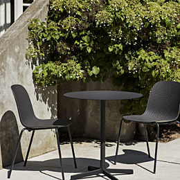 Two black 13Eighty Chairs around a patio table in an outdoor scene