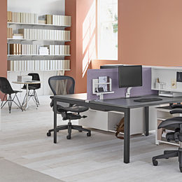 Black Aeron Chairs at aa variety of Layout Studio individual workstations in a shared office space with purple dividing screens and monitor arms.