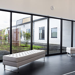 A long, light gray naughtone Clyde Bench with a steel sled base sits at an angle in front of floor-to-ceiling windows.