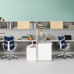 Two Action Office workstations with gray fabric wall panels, white storage units, and blue Mirra 2 ergonomic desk chairs.