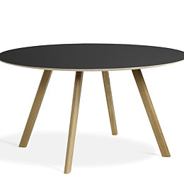 Black, round Copenhague Table with oak base, viewed at an angle.
