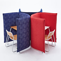 White Bounce Chairs sit at a grouping of three naughtone Cloud 1.5 Desks, two blue, one red, arranged with their high backs together.